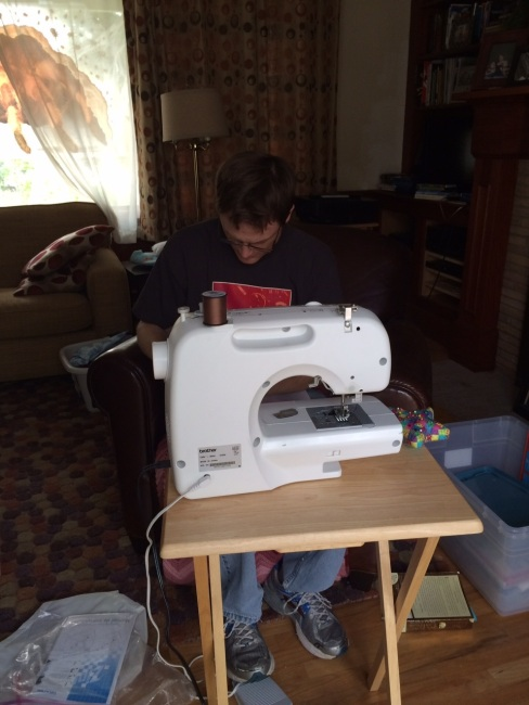 My husband, attempting to sew together my mismatched pieces.